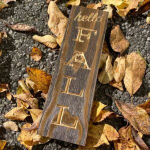 Carved Wooden Sign with the saying Hello Fall vertically. Brown Stain with natural wood color letters. Perfect gift item for that person that loves the fall weather and enjoys decorating their house accordingly.